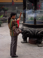 Woman Praying in Temple Courtyard (China)